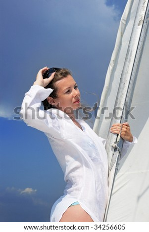 The girl costs on a yacht nose keeping for a sail during a storm