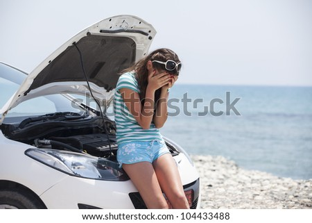 the girl cries over the broken car. Nice girl with the broken auto - stock photo