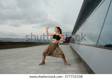 the girl dances on the street. dances on the street. - stock photo