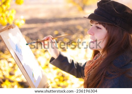 The girl draws on nature autumn landscape - stock photo