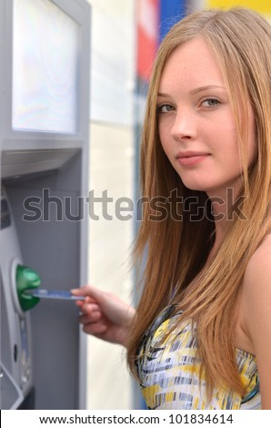 The girl draws out money in a cash ATM - stock photo