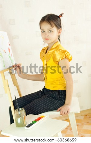 The girl draws sitting at an easel - stock photo