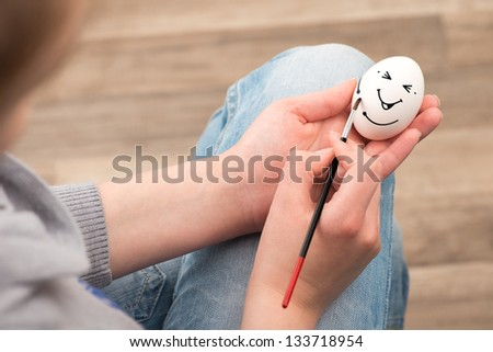 The girl draws with a brush on an white egg. Egg laughs.
