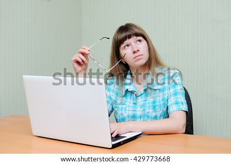 The girl dreams on a workplace at the computer - stock photo