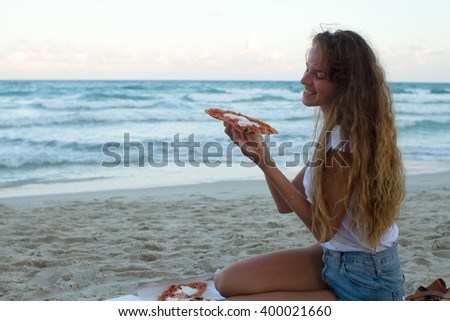 the girl eats pizza on the beach, a dinner at sunset, the girl fashionably dressed eats pizza - stock photo