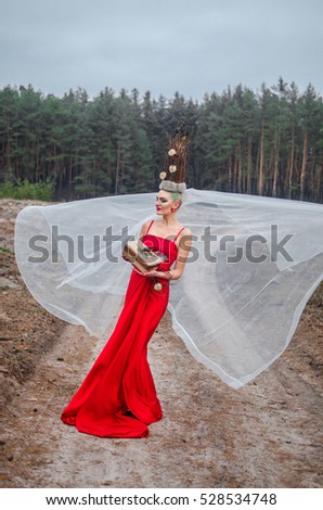 the girl emerges from the woods in a red dress and white veil , on her head a crown of twigs decorated with roses . in the hands of the girls Christmas gift