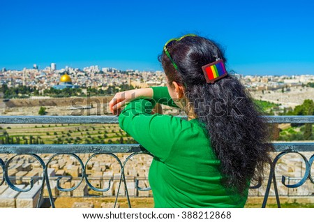 The girl enjoys the view on the old Jerusalem, standing at the viewpoint of the Mount of Olives, Israel. - stock photo