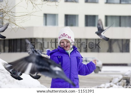 The girl feeds pigeons. - stock photo