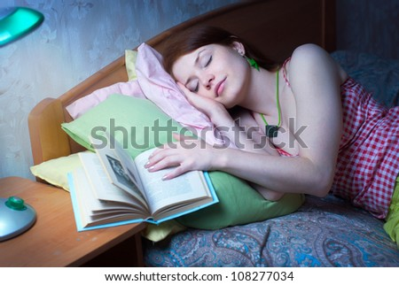 The girl fell asleep with a book, the night - stock photo