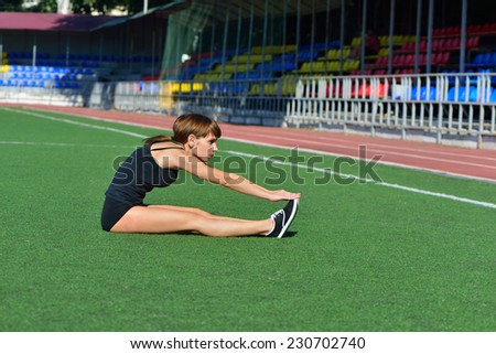 The girl goes in for sports on the football field - stock photo
