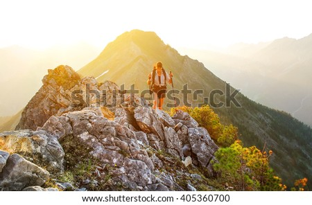 The girl goes in mountains at sunset - stock photo