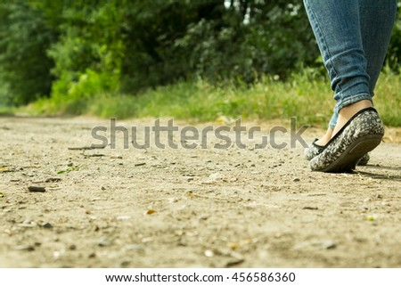 The girl goes on a dirt road with prospect into the distance through the trees