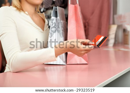 The girl holds a credit card over a counter in shop - stock photo