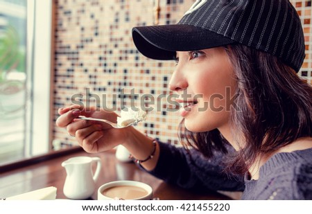 the girl holds a spoon with white cake and smiling - stock photo