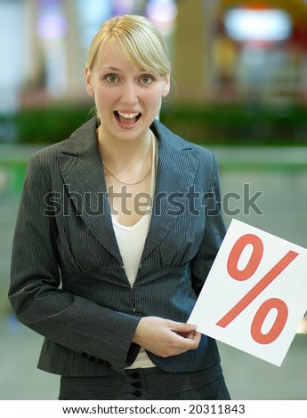 The girl holds in hands a paper with a sign on % - stock photo