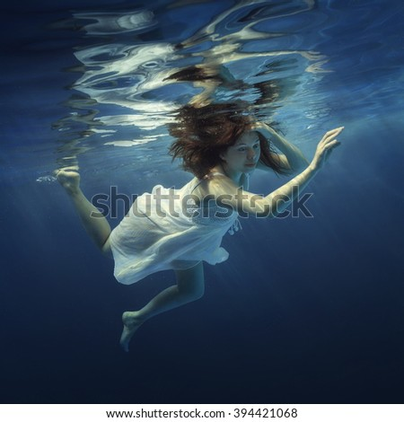 The girl in a beautiful dress under water.
