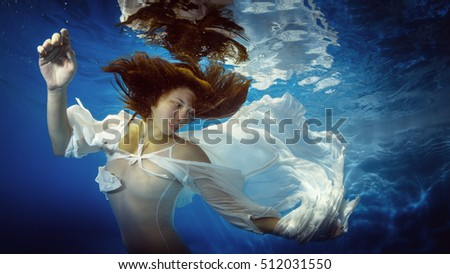 The girl in a beautiful dress underwater