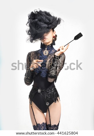 The girl in a beautiful vintage lingerie, holding a whip - stock photo