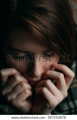 The girl in a blanket with eyes closed and fingers on the face