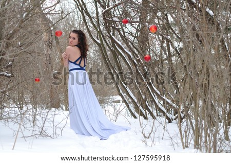 the girl in a dress in the winter. freezes. red apple hangs - stock photo