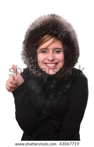 The girl in a fur cap smiles also a hand shows a good sign - stock photo