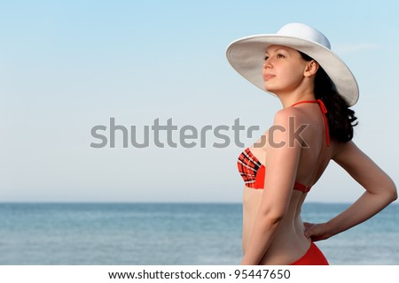 The girl in a hat against the sea and blue sky