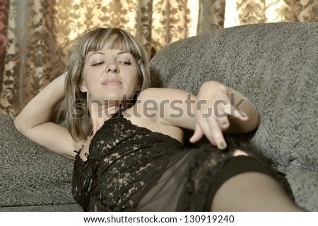 The girl in a interior lies in underwear on a sofa