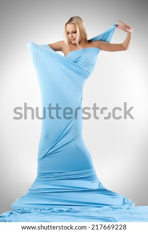 The girl in a long blue dress on a gray background.  - stock photo