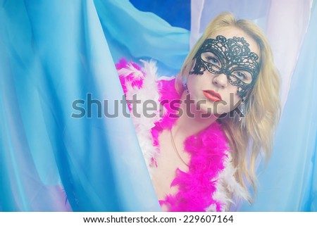 The girl in a mask and a boa - stock photo