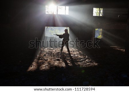 The girl in a military uniform with a rifle in the ruins - stock photo