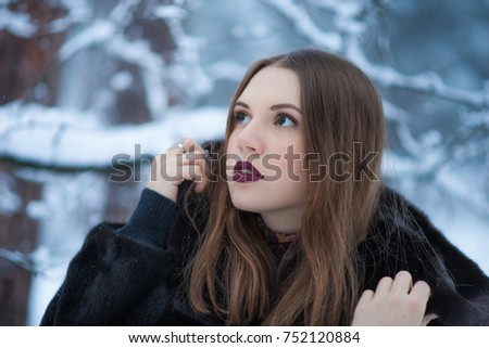 The girl in a mink coat in a snowy forest