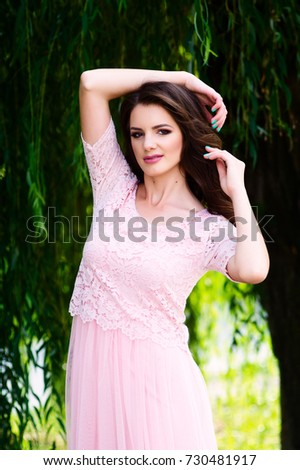 The girl in a pink dress is walking in the park