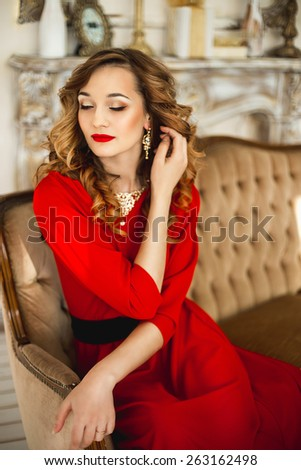The girl in a red dress with a black belt in gold costume jewelry sits near a brown sofa