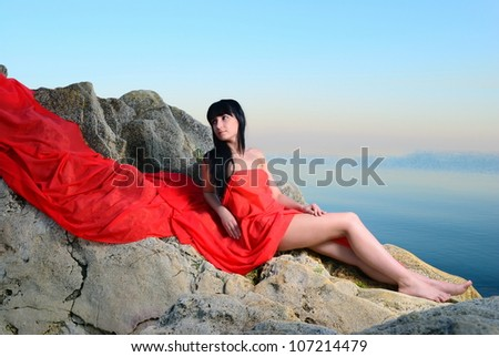 the girl in a red fabric lies on stones near the sea
