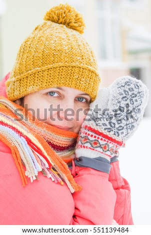 The girl in a red jacket, a colorful scarf and mittens happy walking in the snow in the winter