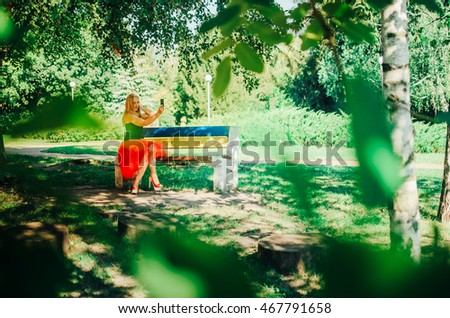 the girl in a red skirt sits in park and reads the book