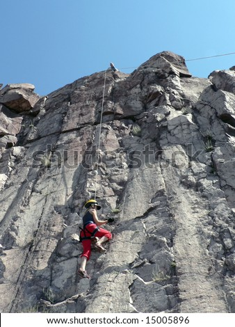 The girl in a red suit is engaged in rocky climbing - stock photo