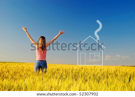 The girl in a wheaten field looks at new home - stock photo