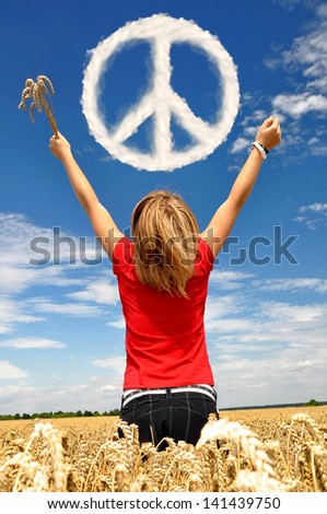 The girl in a wheaten field looks at peace symbol from clouds