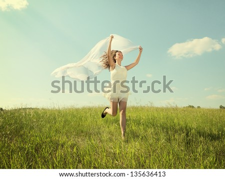 The girl in a white dress runs on a grass