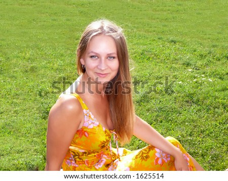 The girl in a yellow dress on a green herb
