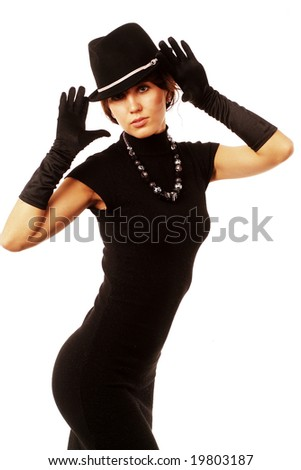 The girl in black clothes on a white background with a hat
