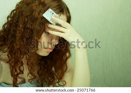 The girl in confusion holds contraceptive tablets in hands - stock photo