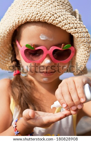 The girl in glasses gets on the palm of sunscreen - stock photo
