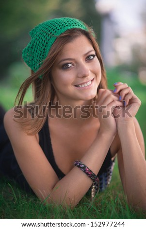 The girl in green knitted beret on the meadow