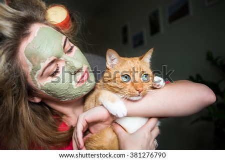 The girl in hair curlers close-up. On the girl's face rejuvenating mask. ginger cat,  - stock photo