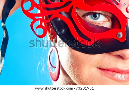 The girl in red to a mask on a blue background - stock photo