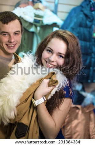 The girl in shop looks a jacket - stock photo