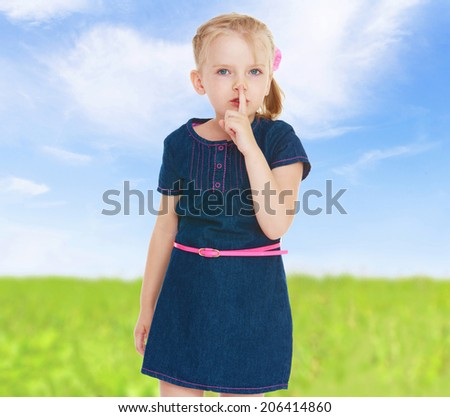 The girl in the blue denim dress shows a sign - quiet!happy childhood, carefree childhood concept. - stock photo