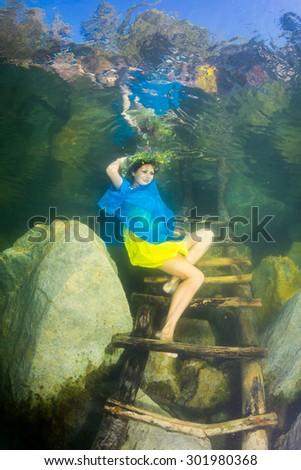 The girl in the dress colors of Ukrainian flag, posing underwater - stock photo